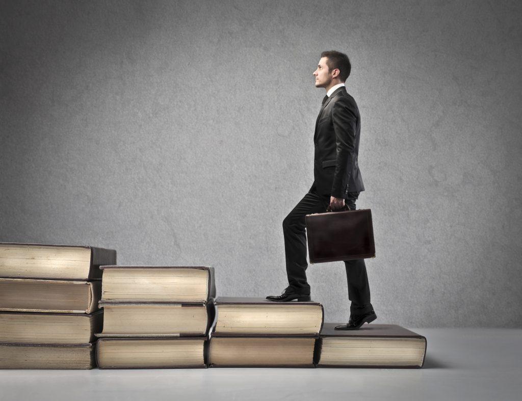 Business man walking up escalating piles of books