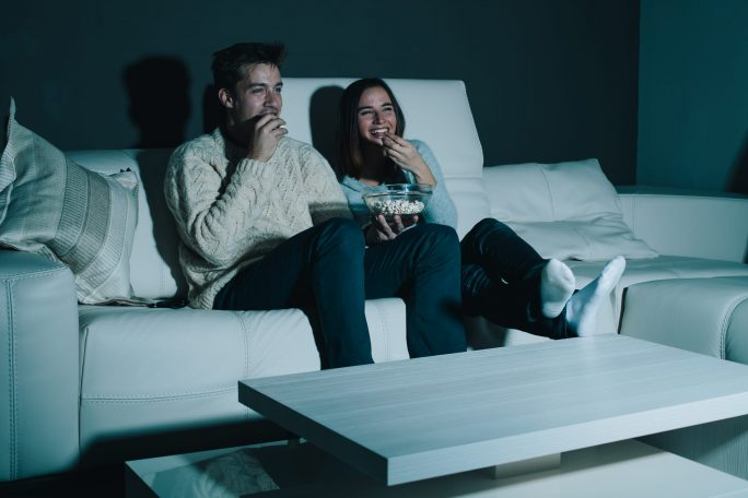 A couple watching a movie at home