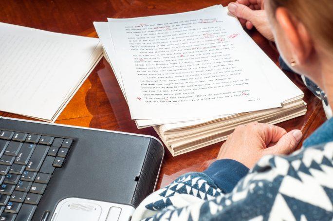 Writer staring at corrected manuscript.