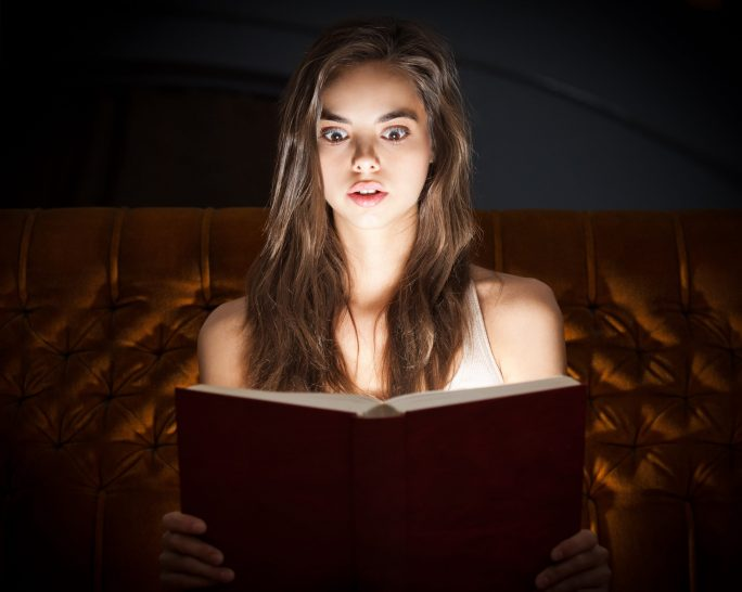 A facinated woman reading a glowing book
