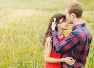 couple innocently embraced in a lovely green field