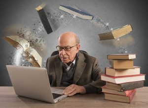 Older Male reading with books flying into the computer screen