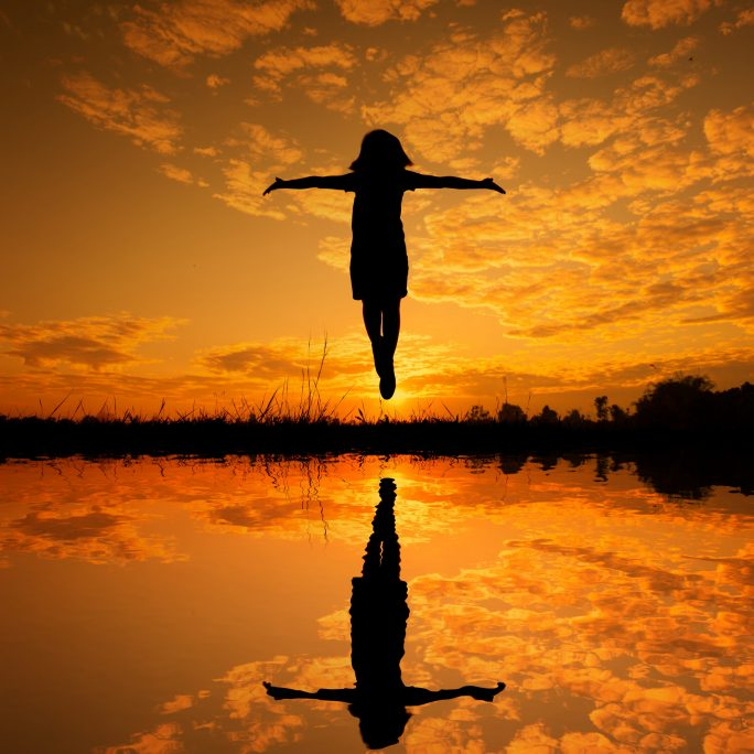 girl levitating in air reflected in golden lake