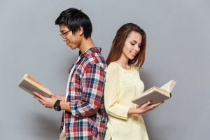 couple standing back to back enjoying reading