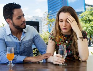 unhappy couple at table with drinks