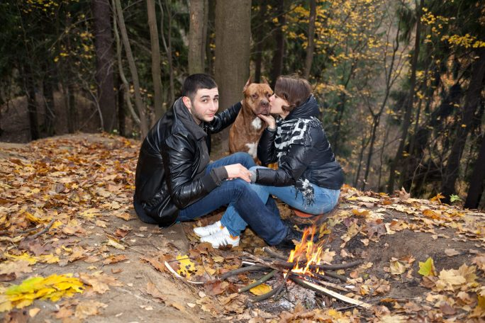 couple with dog sitting in autumn landscape, he looks jealous of attention to dog