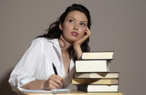woman with stack of books, writing and gazing off