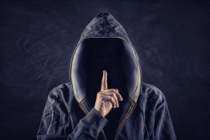figure in a hoody with finger up for silence