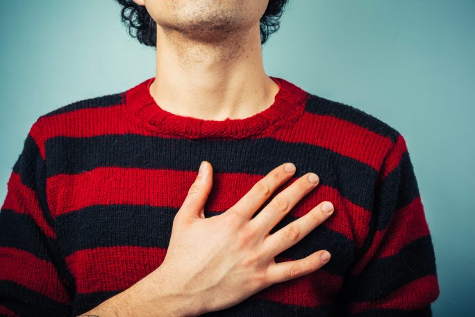 man in striped sweater with hand over heart