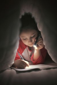 girl writing in blanket fort with flashlight