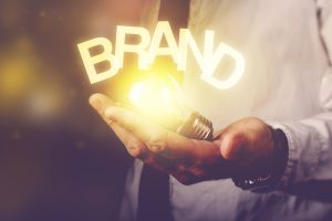 man's hand with glowing lightbulb and the word BRAND