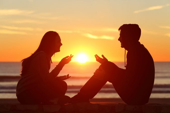 woman and man in silhouette against sunset