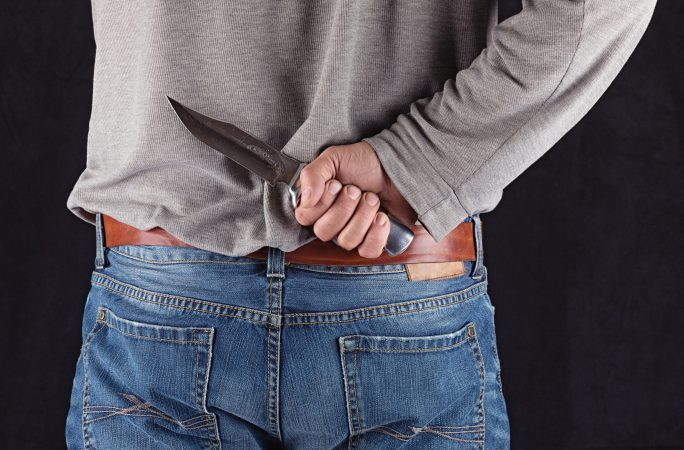 closeup of man with knife behind back
