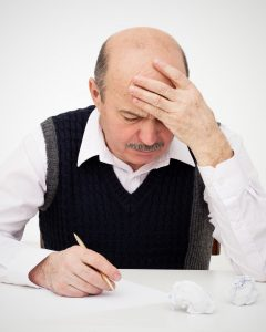man holding head while trying to write
