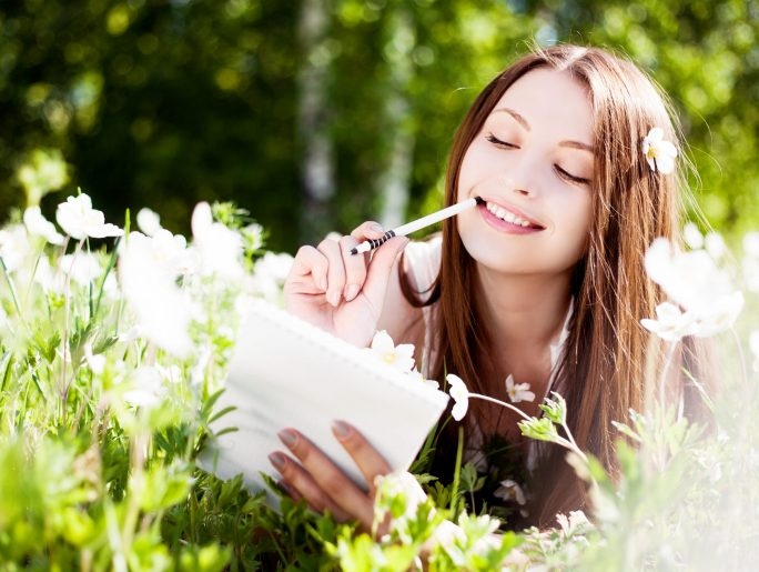 Young woman writing in notebook among wildflowers