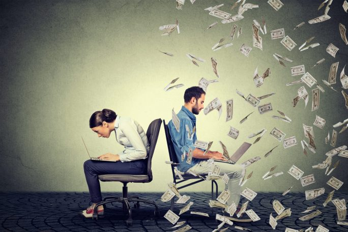 two writers sitting back to back with one spewing money as he types