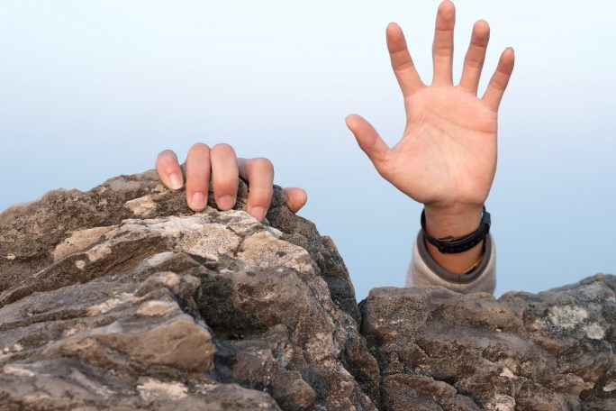 hands reaching over rock in need of rescue