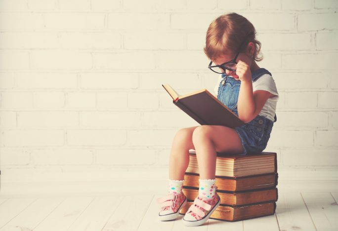 child sitting on stack of books reading