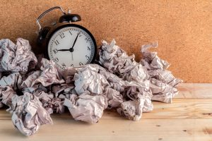 alarm clock surrounded by crumpled papers