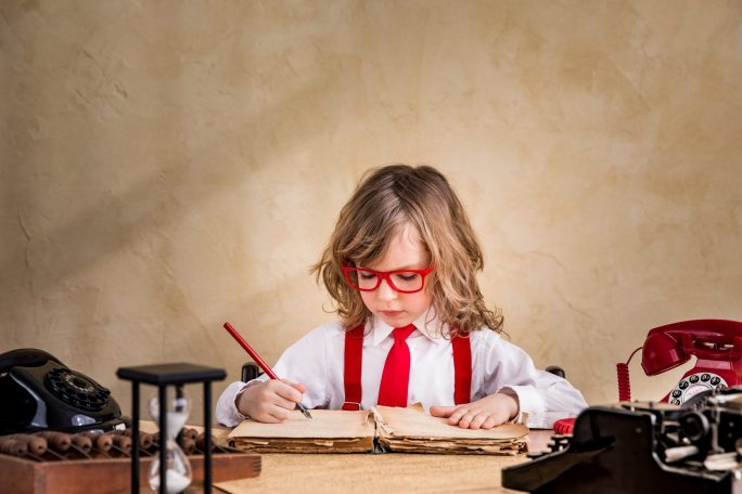 child dressed for business writing in office setting