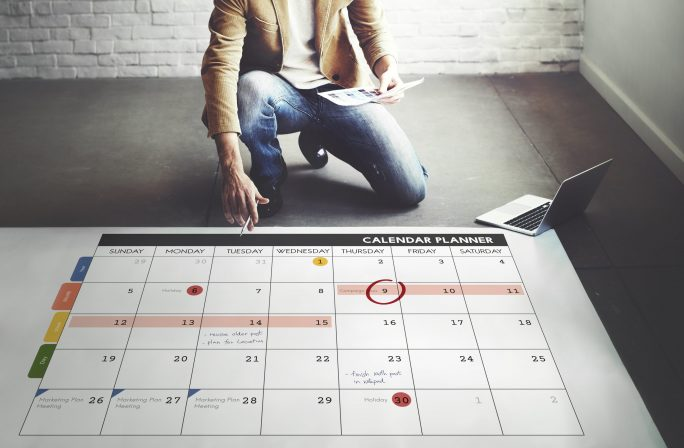 man working with giant calendar on the floor