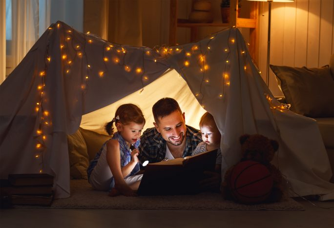 father reading to kids in homemade tent