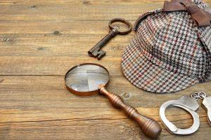 mystery paraphernalia: hat, key, magnifying glass, handcuffs