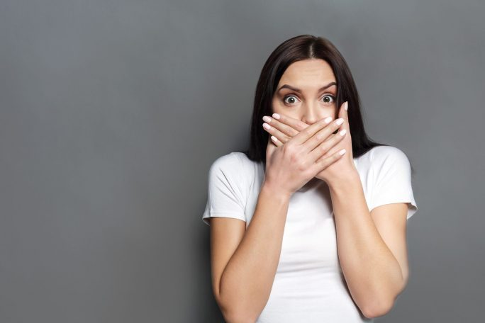 fearful woman covering her mouth with both hands