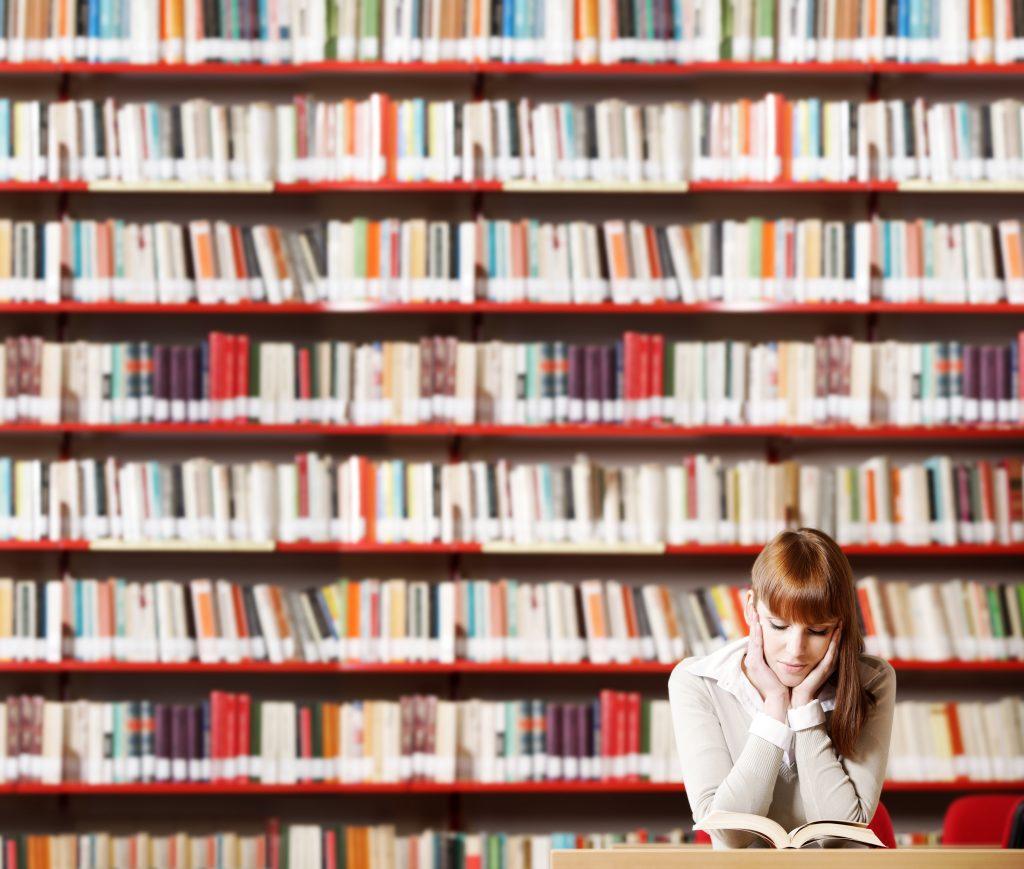 girl reading in front of shelves full of hundreds of books