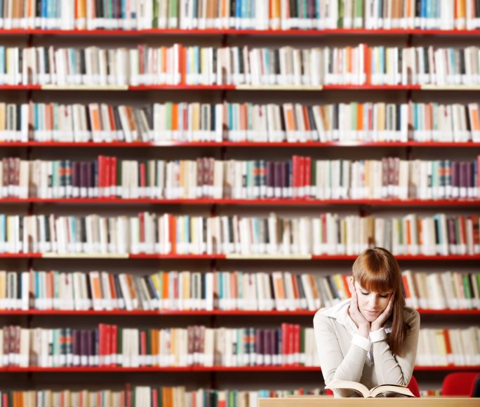 girl reading in front of shelves full of hundreds of books